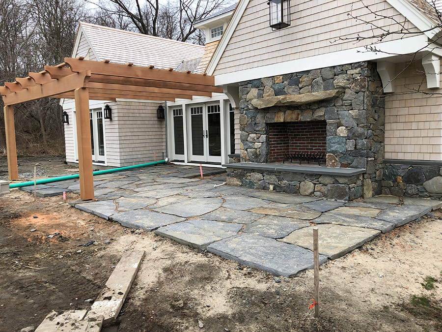 A stone patio and stone fireplace were designed together adding a beautiful touch to this pool house. We worked closely with the architect, DiMauro Architects, Inc.